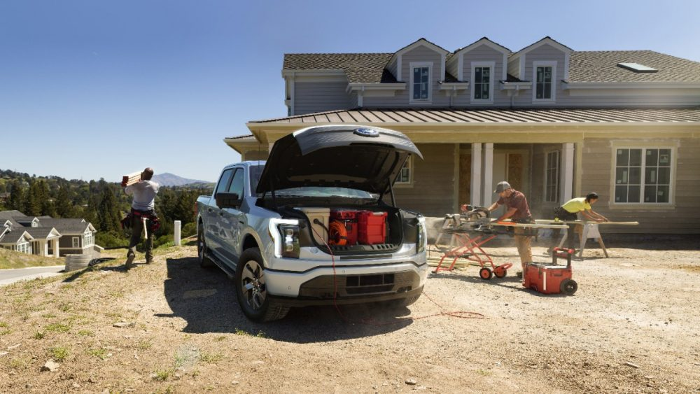 2022 Ford F-150 Lightning Lariat parked next to a partially constructed house with its FRUNK open