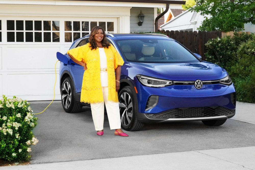 Retta standing in front of a blue Volkswagen ID.4 in a driveway