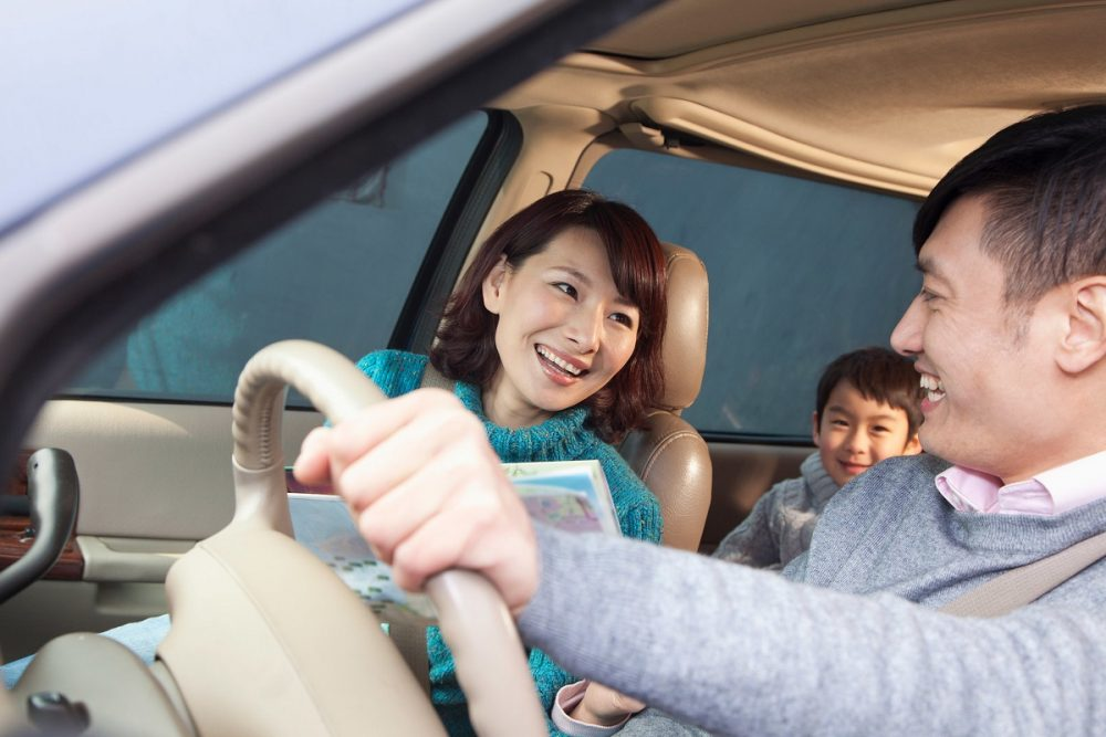 asian family in car on road trip