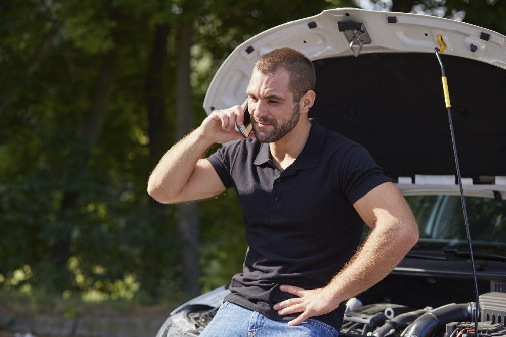 Man on cell phone sitting on hood of broken down vehicle