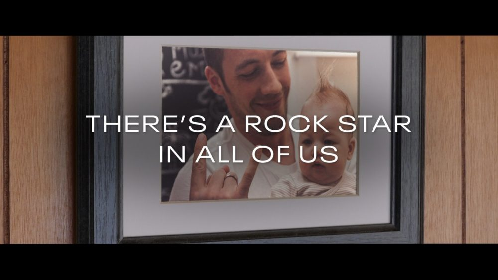 """A still from the """"Rock Star"""" spot, showing a father and child in a picture frame. The text, """"THERE'S A ROCK STAR IN ALL OF US,"""" covers the photo."""