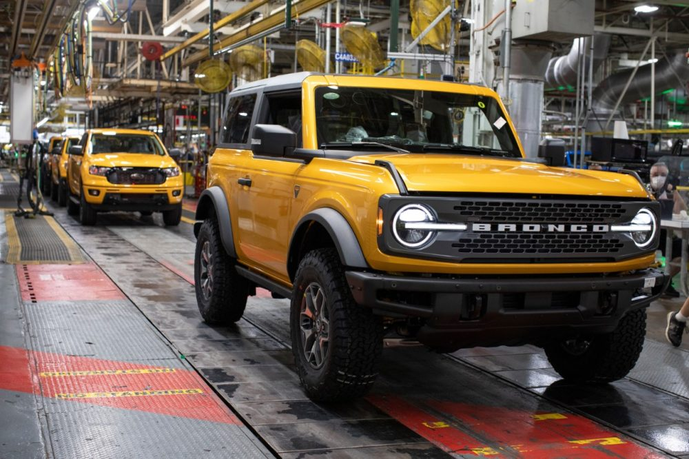 A Cyber Orange Ford Bronco two-door on the MAP assembly line in front of a nearly finished Ford Ranger