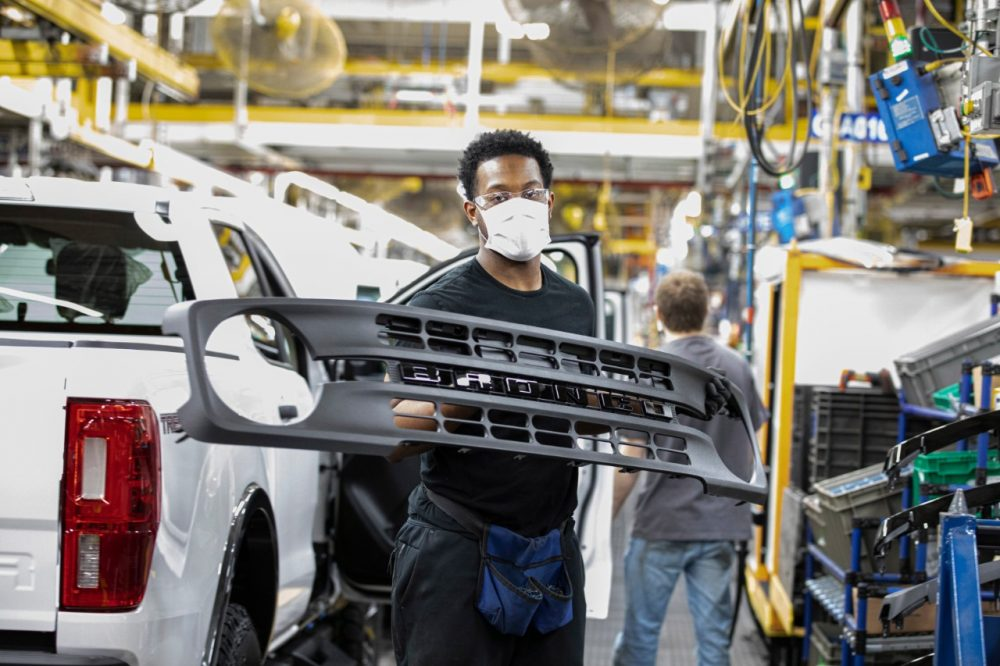 An employee at Michigan Assembly Plant holding the single-piece grille of a Bronco
