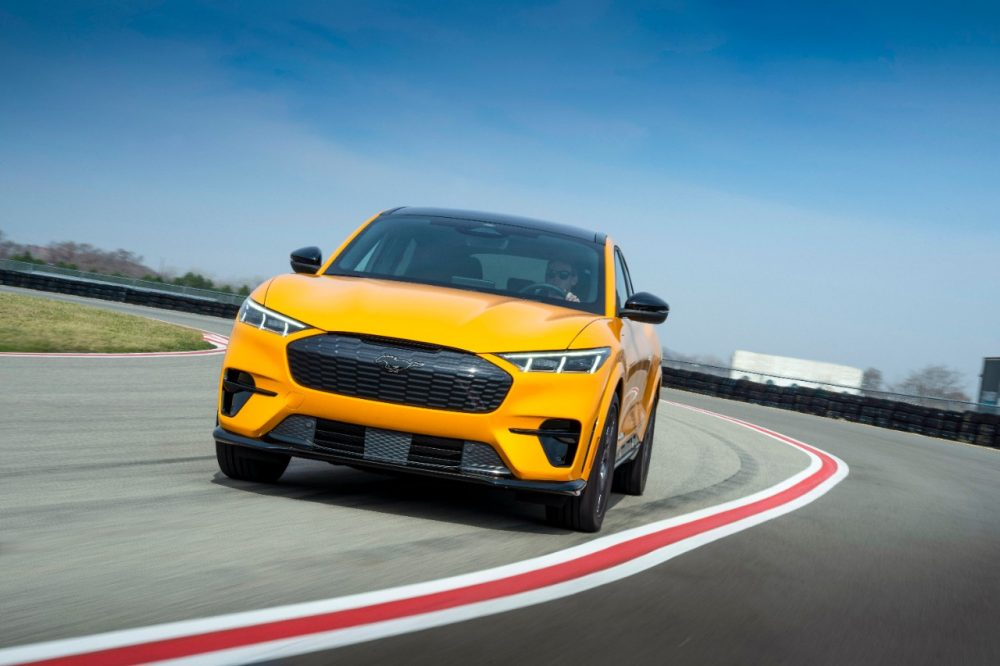 2021 Ford Mustang Mach-E GT Performance Edition in Cyber Orange rounding a corner on the track
