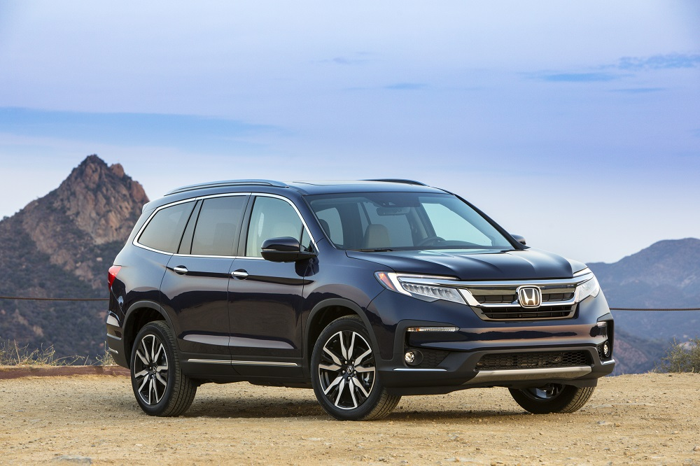 2021 Honda Pilot Elite parked on a sandy surface with rocks and mountains in the background