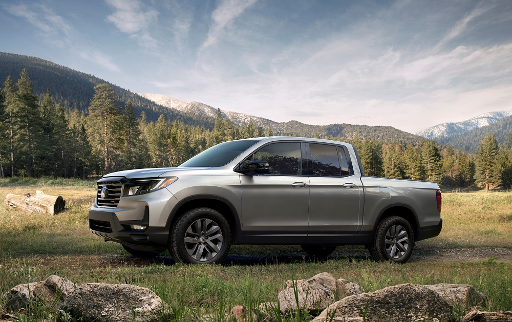 Honda Ridgeline parked in a field with mountains in the background. The Honda Ridgeline was ranked 6th in the 2021 American-Made Index
