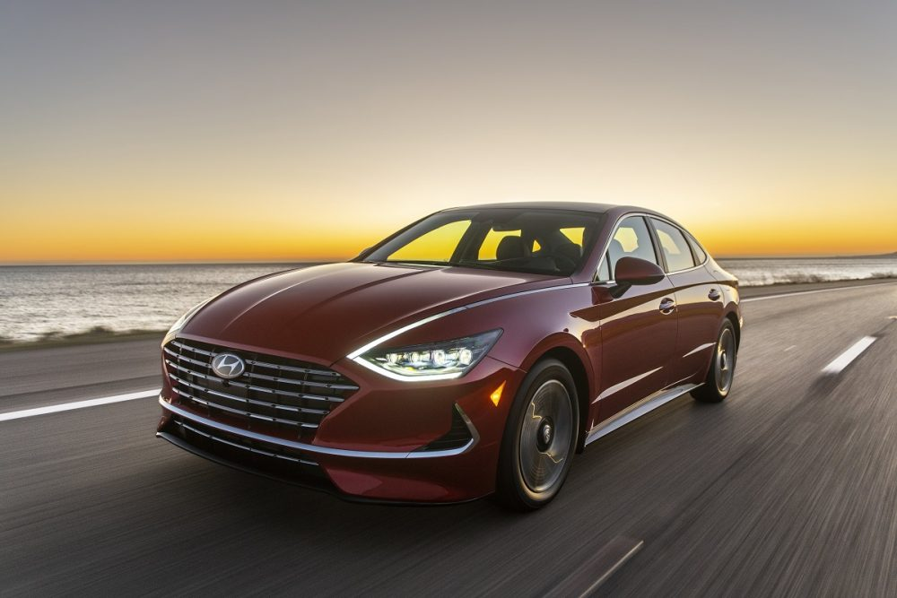 Front side view of 2021 Sonata Hybrid driving down road with headlights on