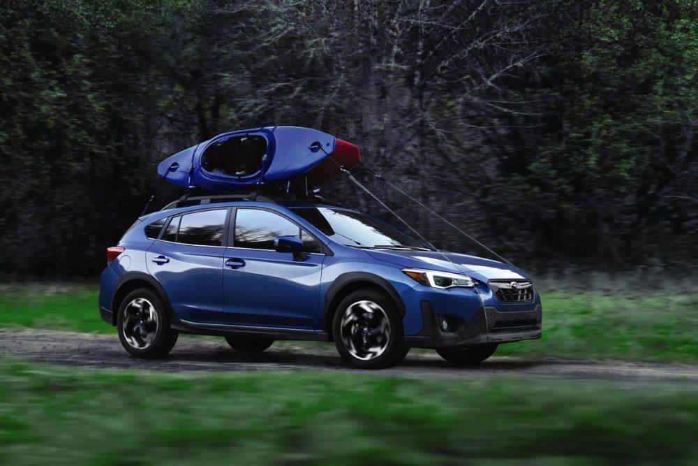 A blue 2021 Subaru Crosstrek with a blue kayak atop drives across an off-road trail