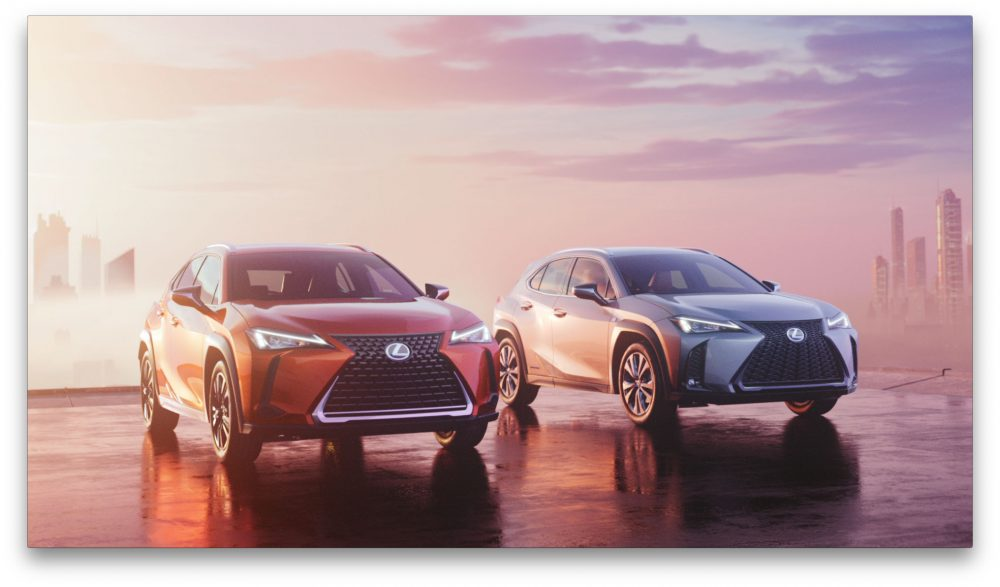 Red and silver 2021 Lexus UX models parked side by side in front of a sunset