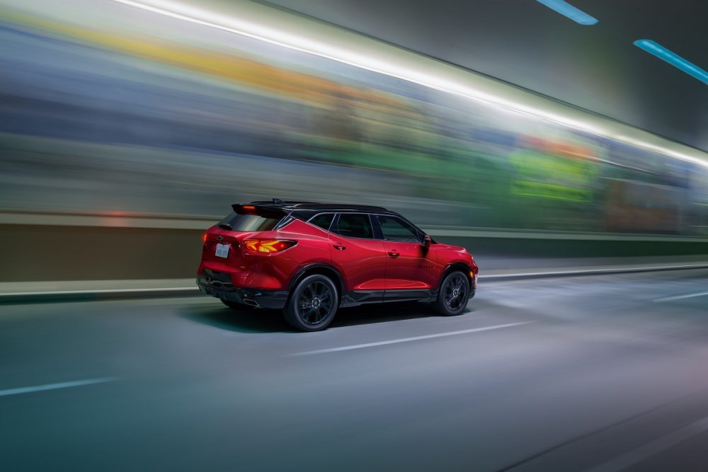 Rear side view of red 2022 Chevrolet Blazer RS with black roof driving down street
