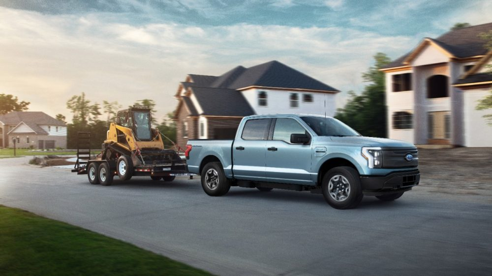 2022 Ford F-150 Lightning Pro hauling a piece of machinery though a new subdivision