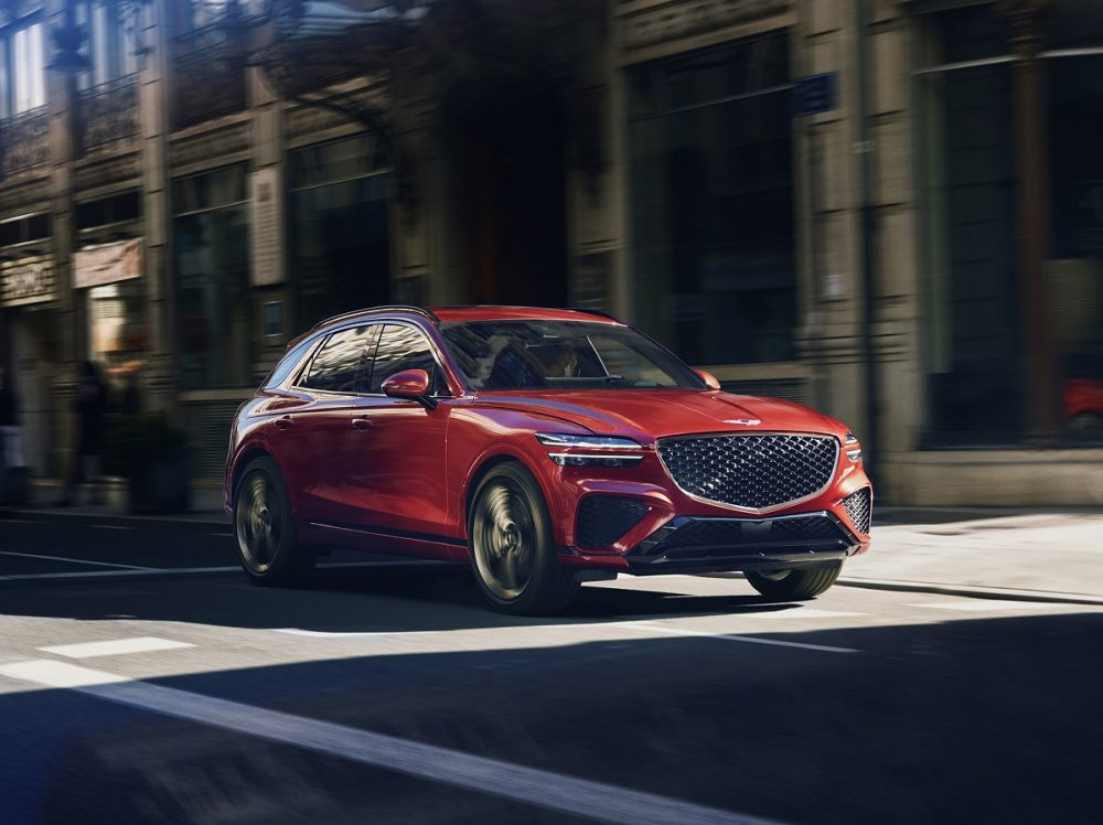 Front side view of 2022 Genesis GV70 driving in shadows on street