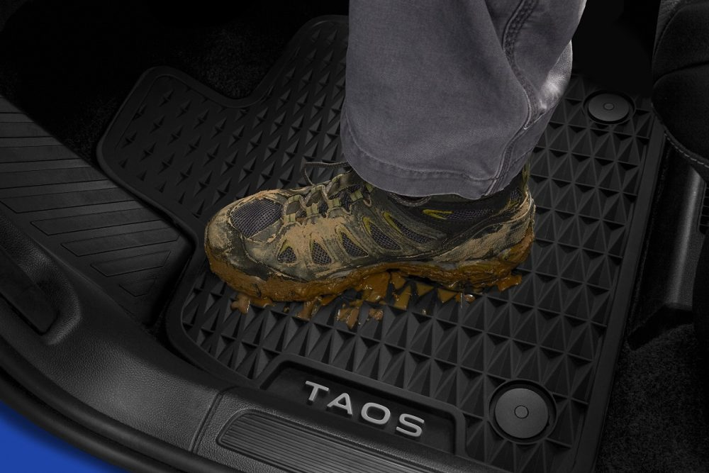 A muddy boot on a rubber MuddyBuddy mat inside the 2022 Volkswagen Taos