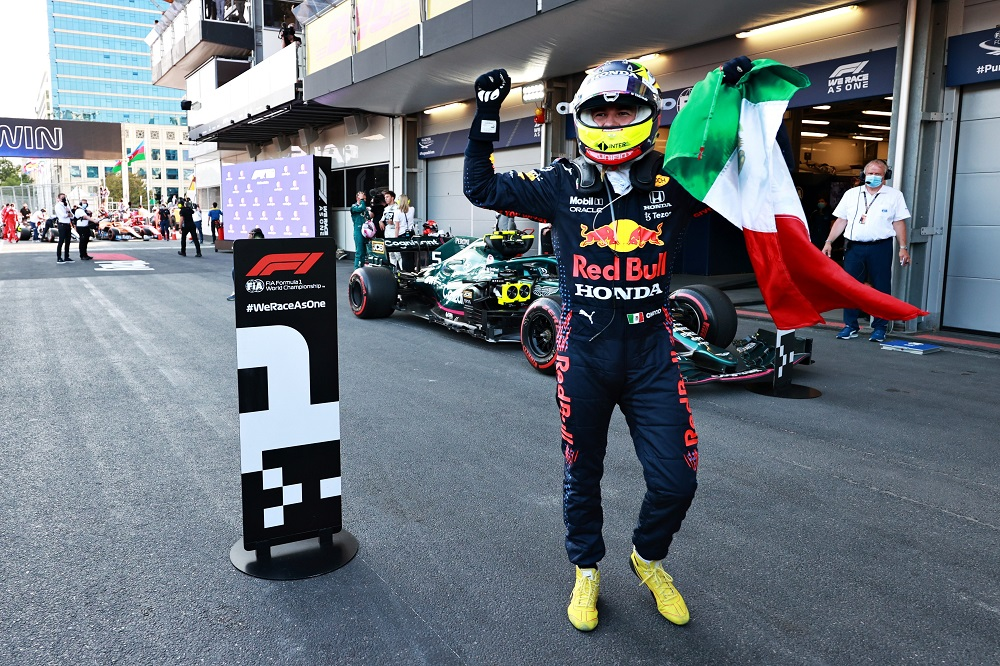 Perez celebrates after the race, holding Mexican flag