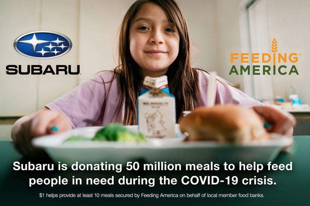 Subaru Feeding America young girl with food tray smiling at camera