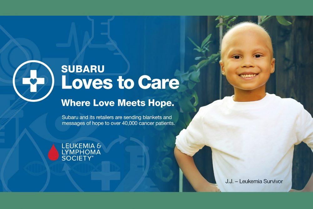 Leukemia survivor JJ proudly standing next to Subaru Loves to Care logo