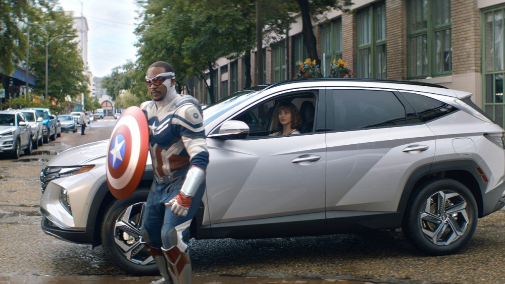 Still photo from ad: Captain America holds shield while standing next to 2022 Hyundai Tucson