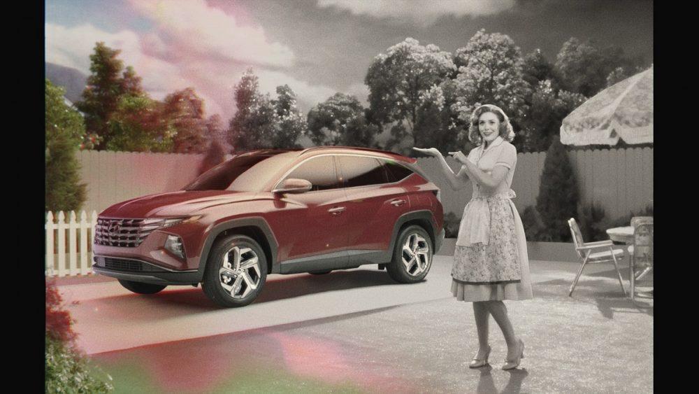 Ad still: black-and-white Wanda Maximoff stands next to red 2022 Hyundai Tucson