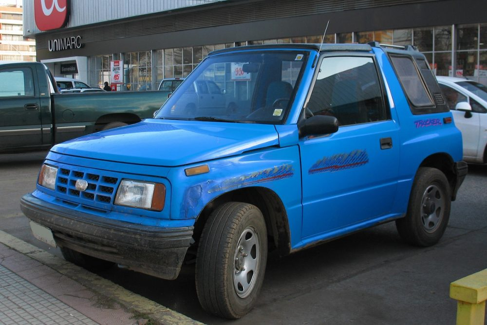 A bright blue 1991 Geo Tracker Convertible is parked in front of a shop