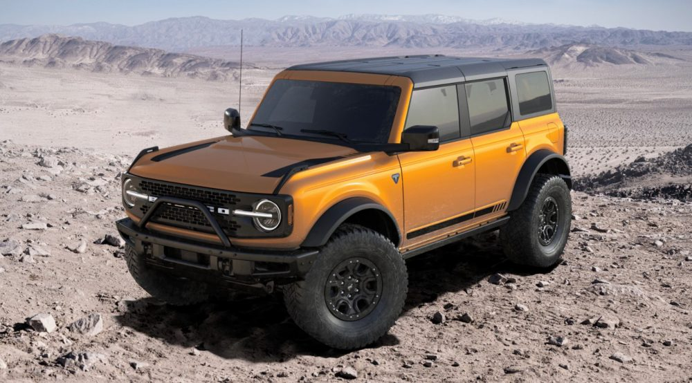 A 2021 Ford Bronco First Edition four-door in Cyber Orange sitting against a desert background