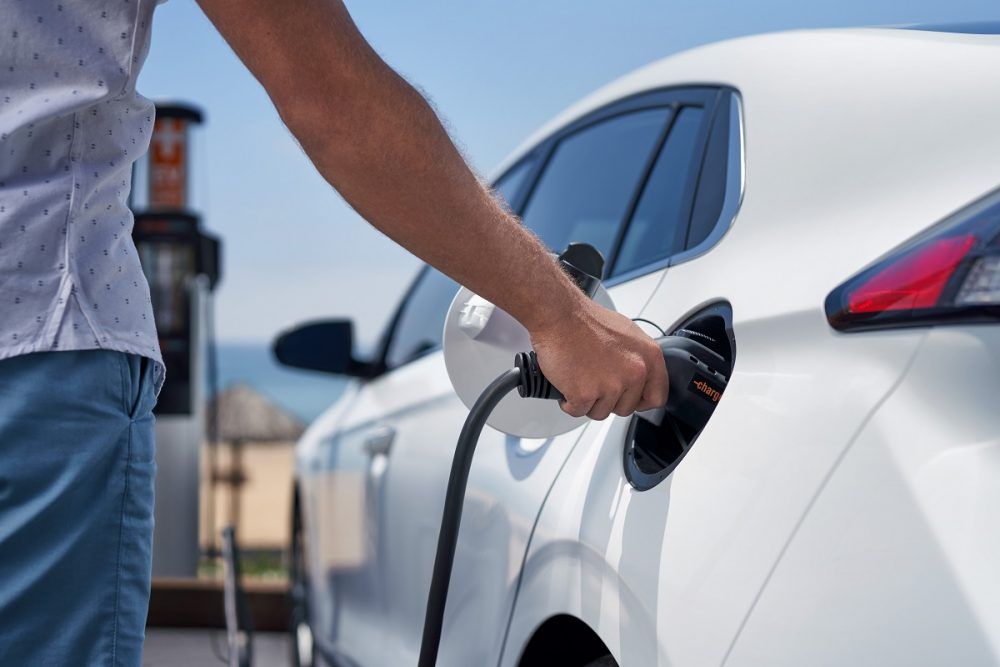 Close-up of person plugging charging cable in to 2021 Hyundai Ioniq Electric