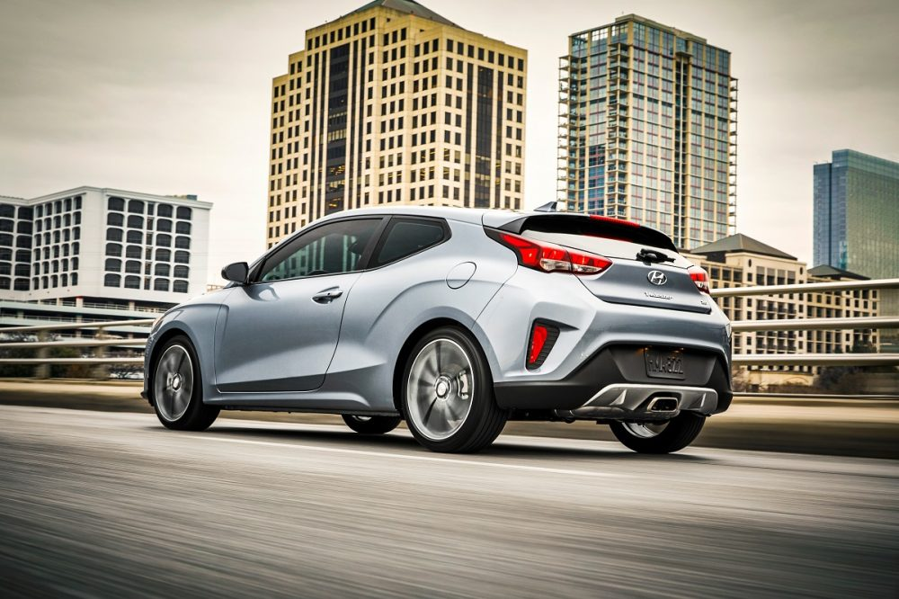 Rear side view of 2021 Hyundai Veloster driving with city skyline in background