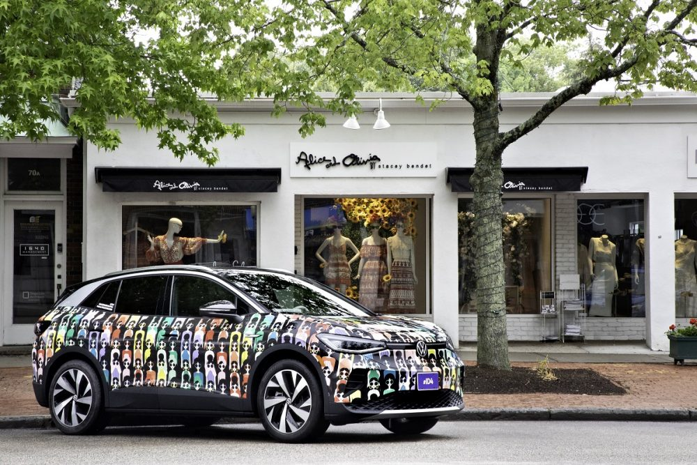 A Volkswagen ID.4, wrapped in an alice and olivia Pride Month design, is parked in front of the alice and olivia storefront
