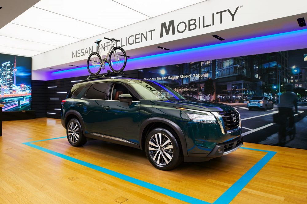 Sideview of 2022 Nissan Pathfinder with bicycle attached to roof rack in Nissan Studio in Canada
