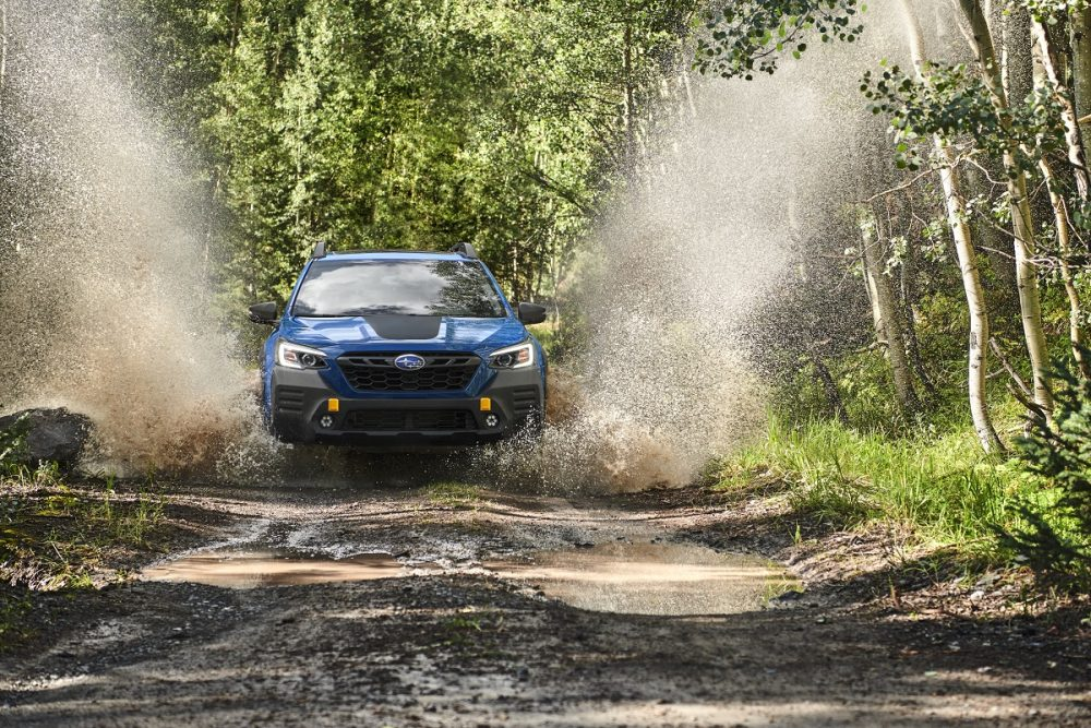 Blue 2022 Subaru Outback Wilderness Edition rolls down muddy trail and splashes on nearby trees