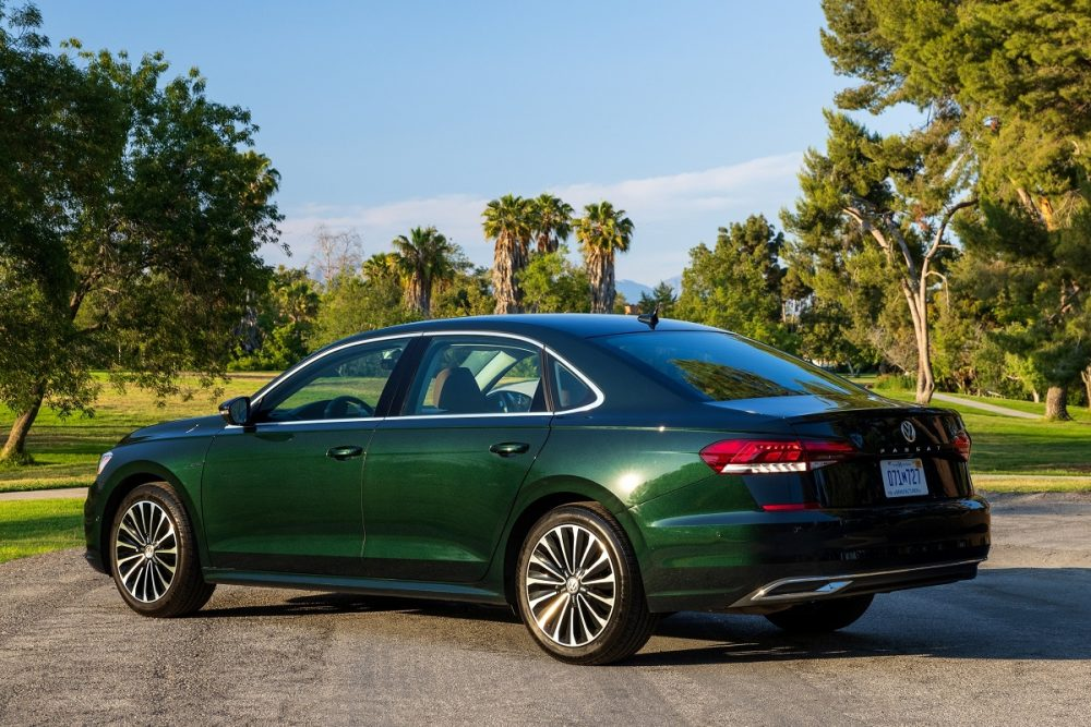 Side rear photo of a Racing Green Metallic 2022 Volkswagen Passat Limited Edition model parked in front of a grassy area