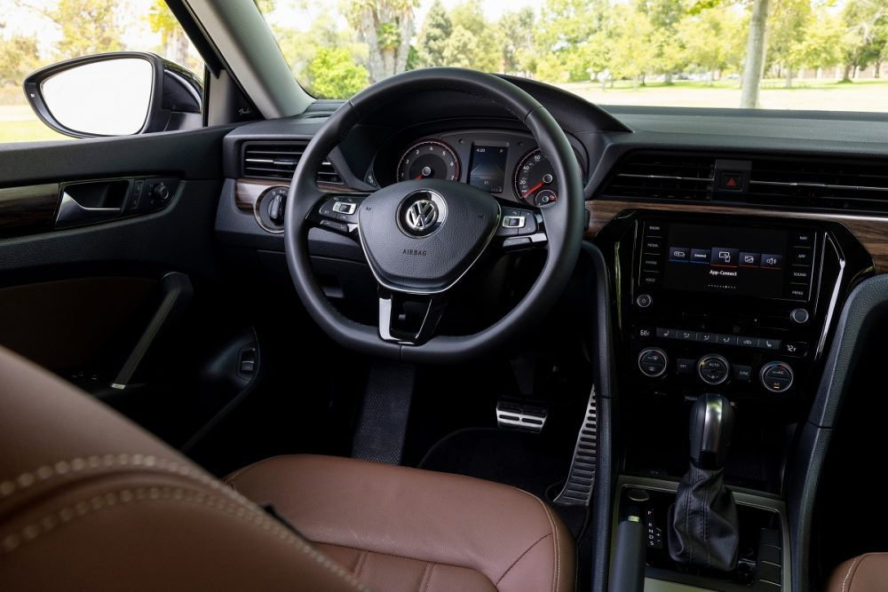 Close up of 2022 Volkswagen Passat Limited Edition driver's seat, steering wheel, and dashboard with black and brown accents