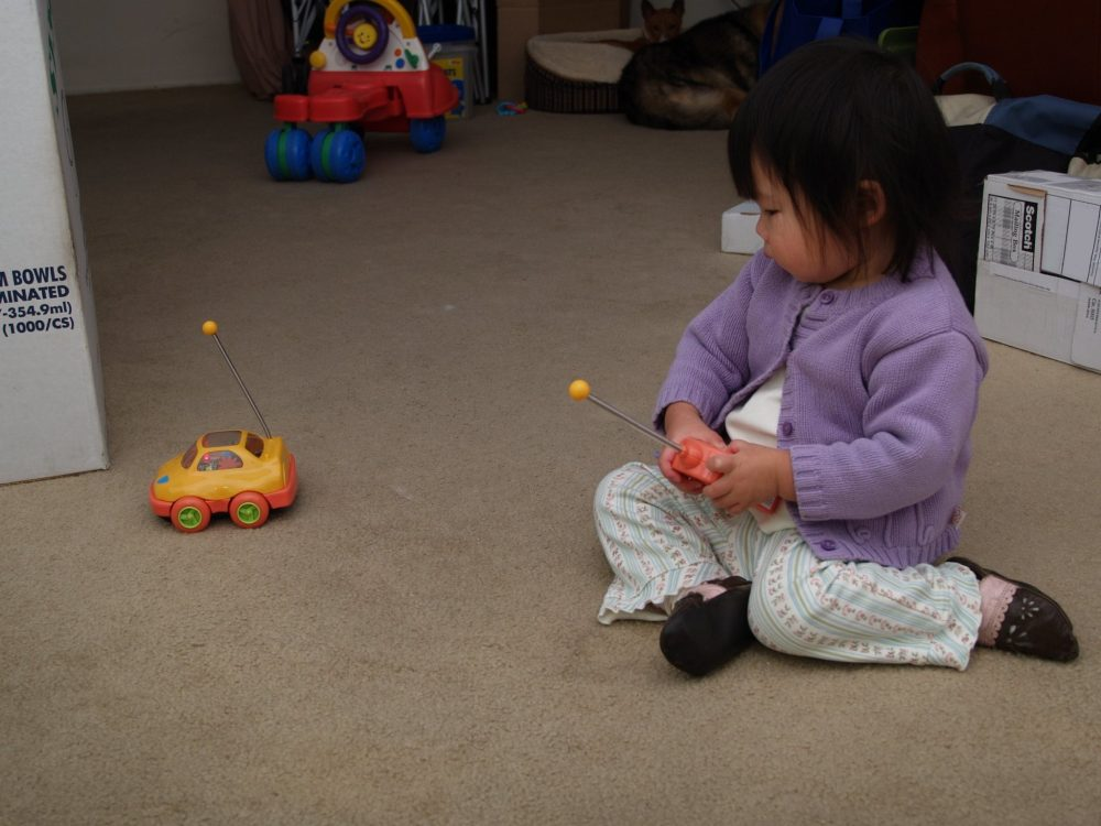 toddler playing with a remote control car