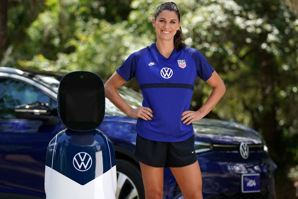 Volkswagen Ambassador Alex Morgan poses in front of a VW ID.4 with the CHAMP robot