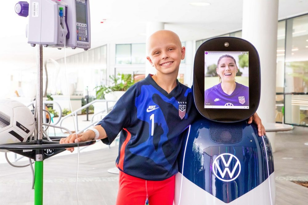 Cancer patient and soccer player Luna Perrone poses with the CHAMP robot with Alex Morgan's face displayed on its screen