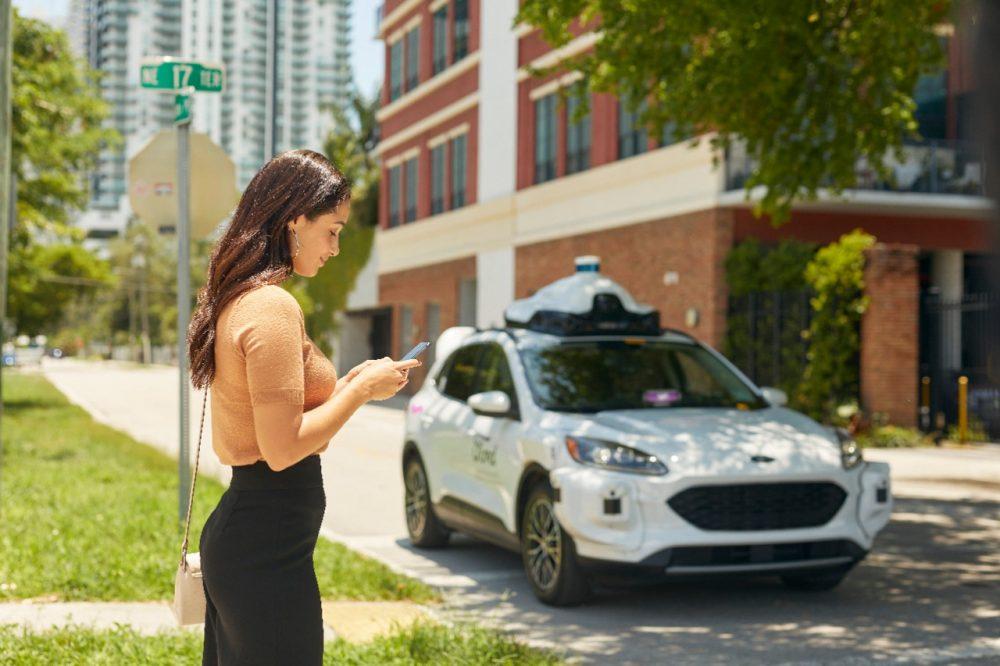 Woman hailing an autonomous Ford Escape through Lyft