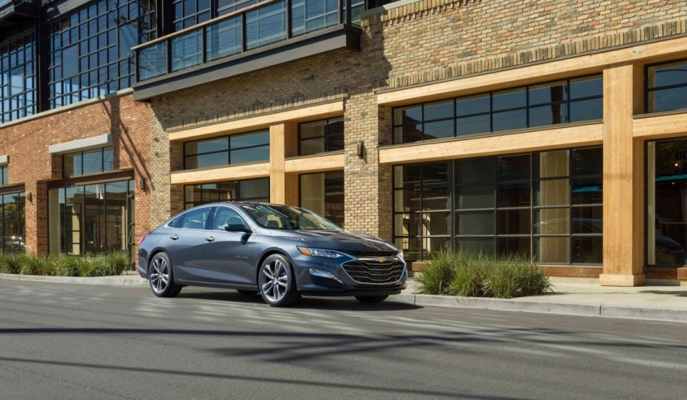 The 2019 Chevrolet Malibu Premier in front of a building