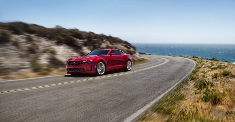Front side view of red 2021 Chevrolet Camaro driving around the curve of a mountainous road with a body of water in the background