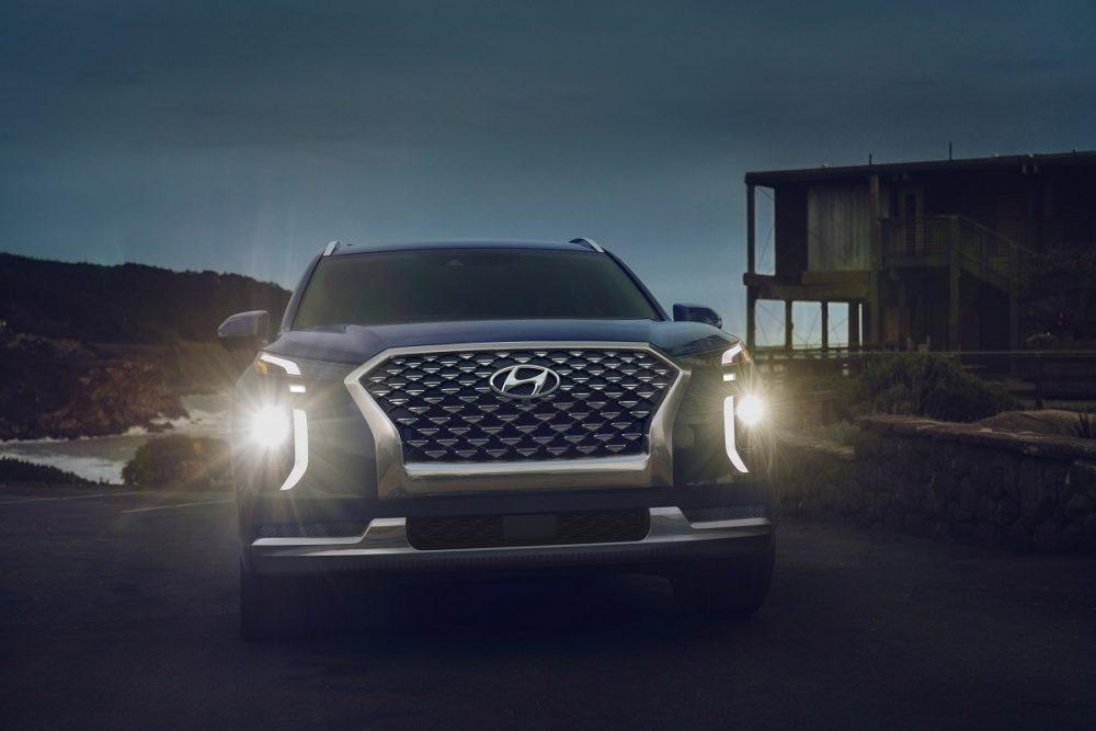 Front view of 2021 Hyundai Palisade at night with LED headlights shining