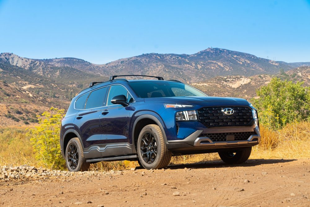 Front side view of 2022 Hyundai Santa Fe XRT on dirt path with mountain backdrop