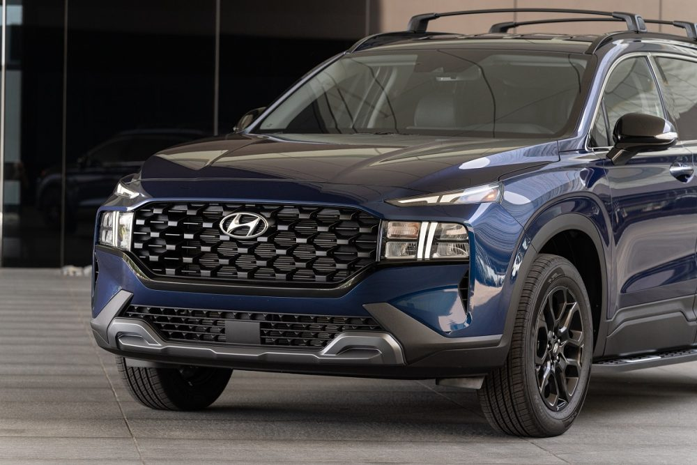 A close-up view of the 2022 Hyundai Santa Fe XRT's headlights, grille, front bumper, and front fender