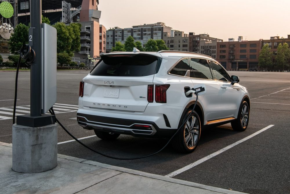 Exterior rear view of the 2022 Kia Sorento PHEV at sunset while it's getting charged