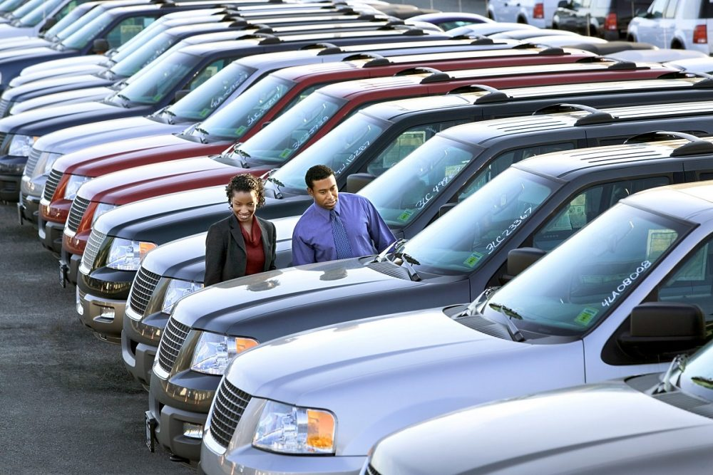 new cars parked on a dealership lot with a man and woman browsing