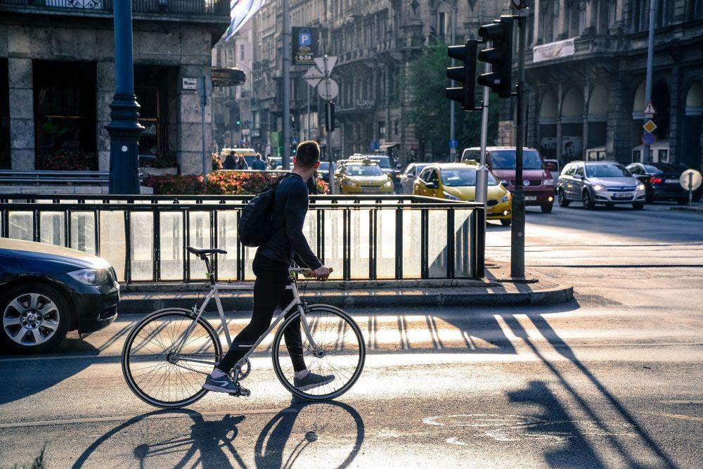 cyclist walking his bike in a bike lane on a busy city street.