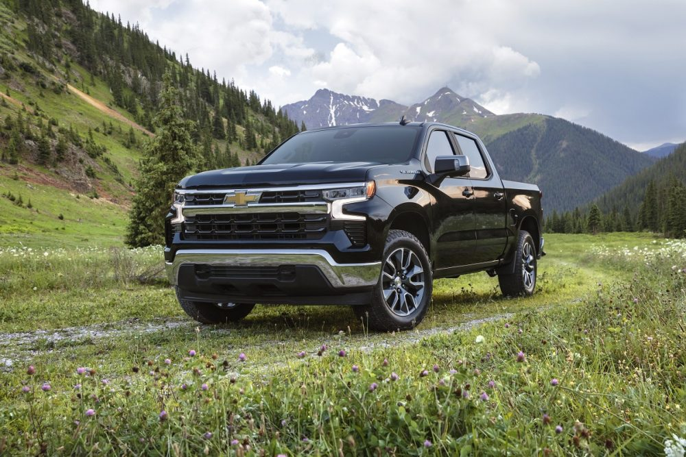 Front side view of 2022 Chevrolet Silverado 1500 LT parked on gravel and grass with mountains in background
