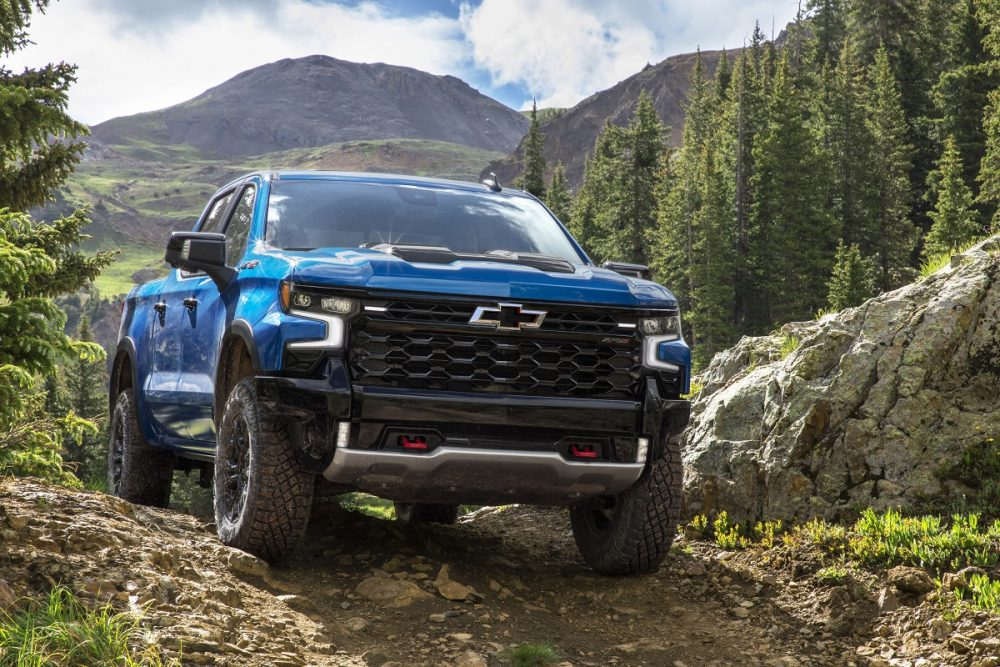 Front view of 2022 Chevrolet Silverado 1500 ZR2 driving on hilly dirt road with mountains in background