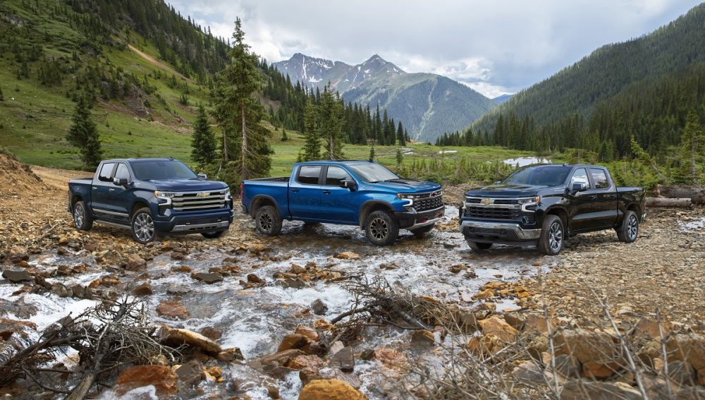 From left, the 2022 Chevrolet Silverado 1500 High Country, ZR2, and LT trims are shown in a rocky stream with mountains in the background