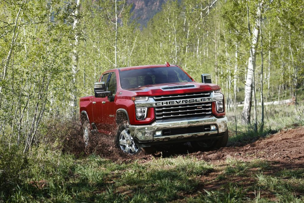 A red 2022 Chevrolet Silverado 2500HD drives through a forest area