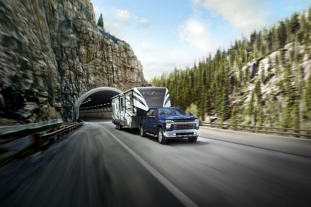 A blue 2022 Chevrolet Silverado 2500HD towing a trailer drives out of a tunnel