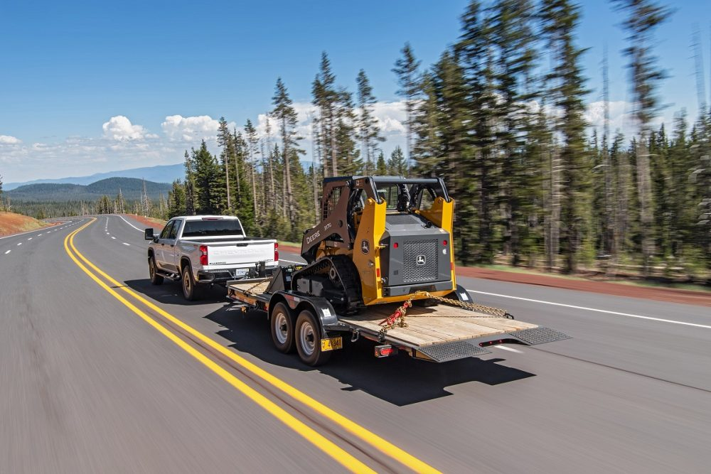A white 2022 Chevrolet Silverado 2500HD tows work equipment on a highway