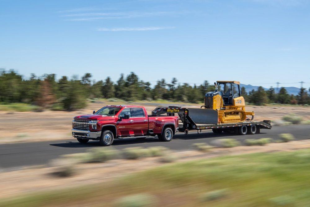 A red 2022 Chevrolet Silverado 3500HD tows work equipment